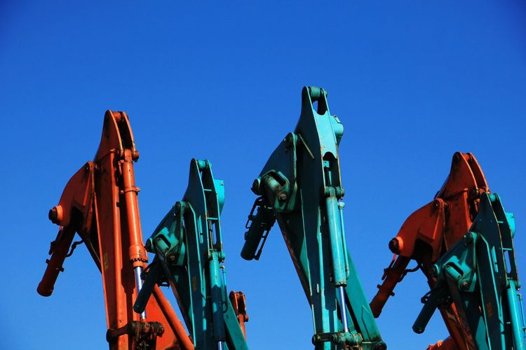 Low angle view of cranes against clear blue sky