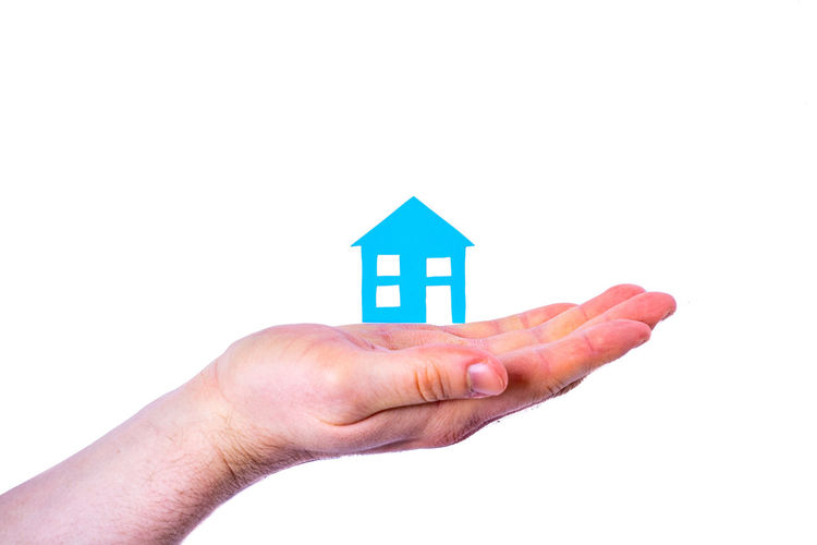 Close-up of hand holding small house against white background