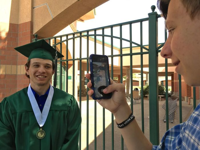 Man photographing brother in graduation gown at college campus