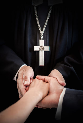 Midsection Of Priest Holding Couple Hands During Wedding