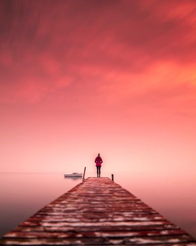 Man standing on pier over sea against sky during sunset