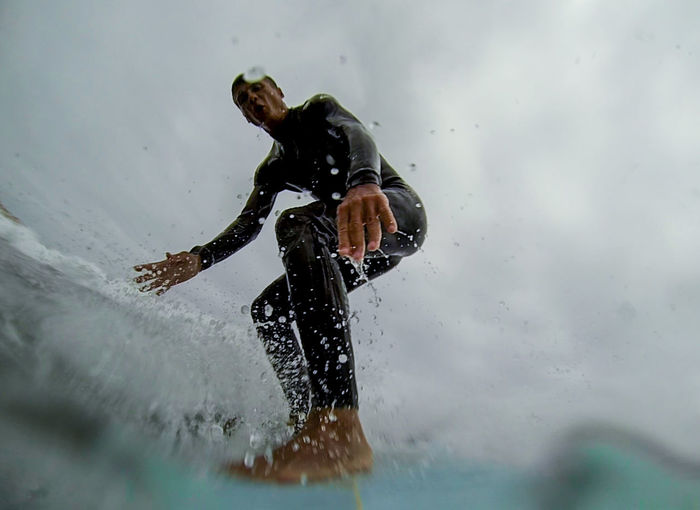 Low Angle View Of Mature Man Surfing On Sea Against Cloudy Sky