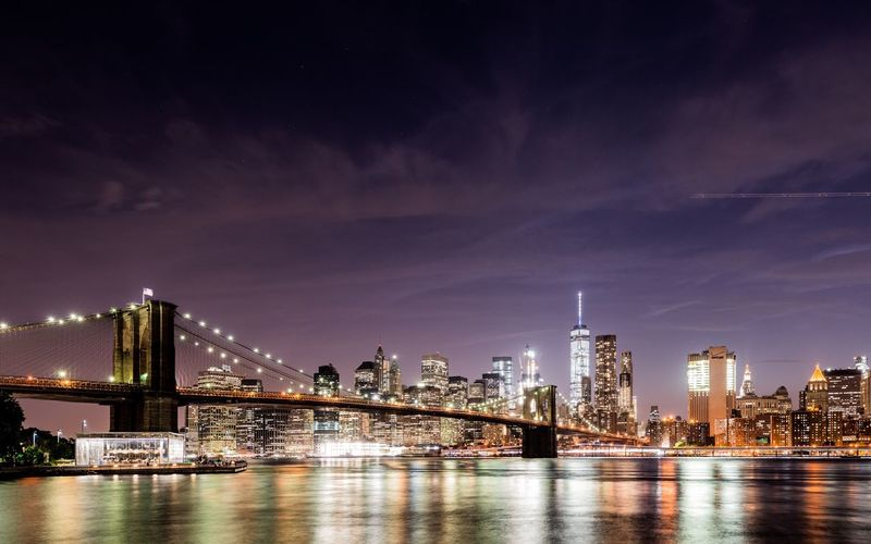 Manhattan Bridge Over East River By Illuminated Cityscape At Night