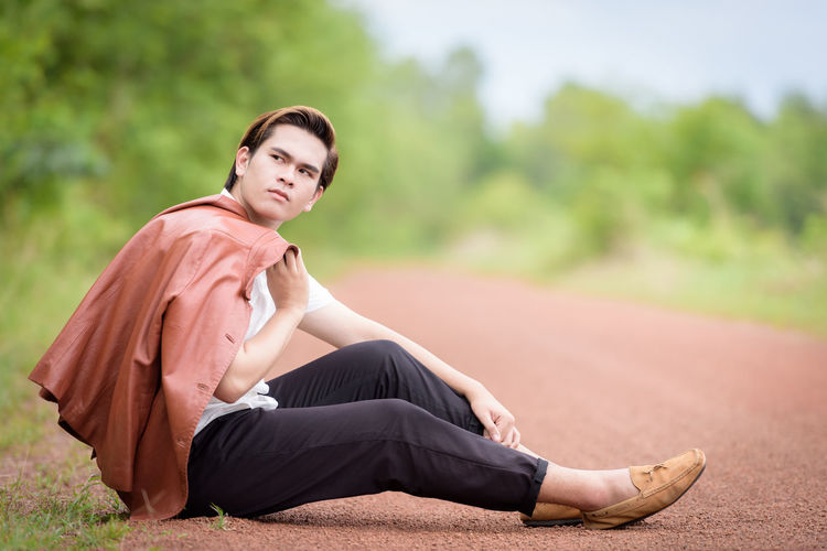 Side view of young man sitting on dirt road against trees