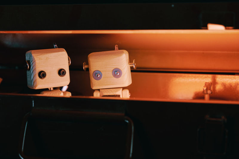 Small wooden robots locked in a metal box. hide from problems and the outside world