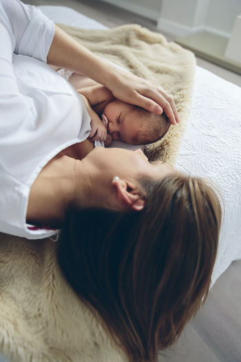 Mother with daughter lying down on bed at home