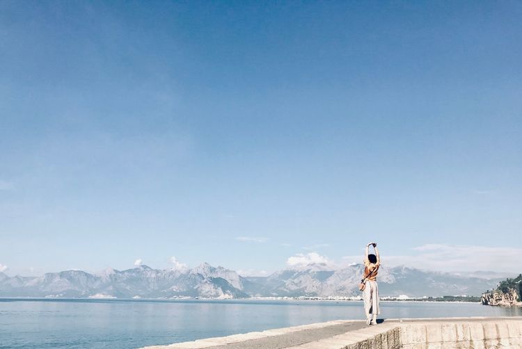 Woman Looking At Sea Against Blue Sky