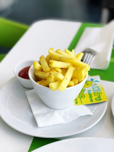 Close-Up Of French Fries With Sauce In Plate On Table