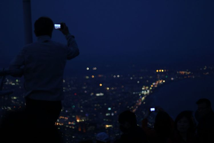 Rear view of woman standing in illuminated city at night
