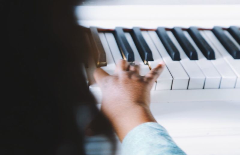 Cropped hand of child playing piano