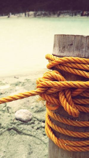 Close-up Of Yellow Rope Tied On Wooden Post By Lake
