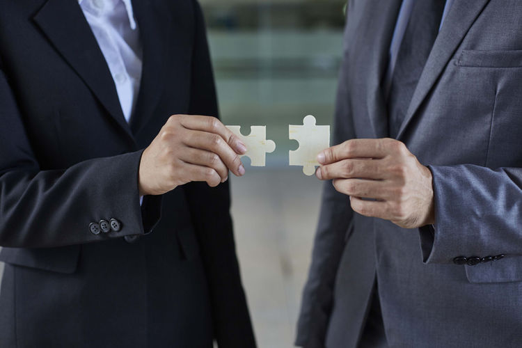 Midsection Of Business People Holding Jigsaw Pieces At Office