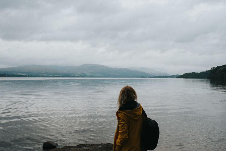 Woman looking at lake against sky