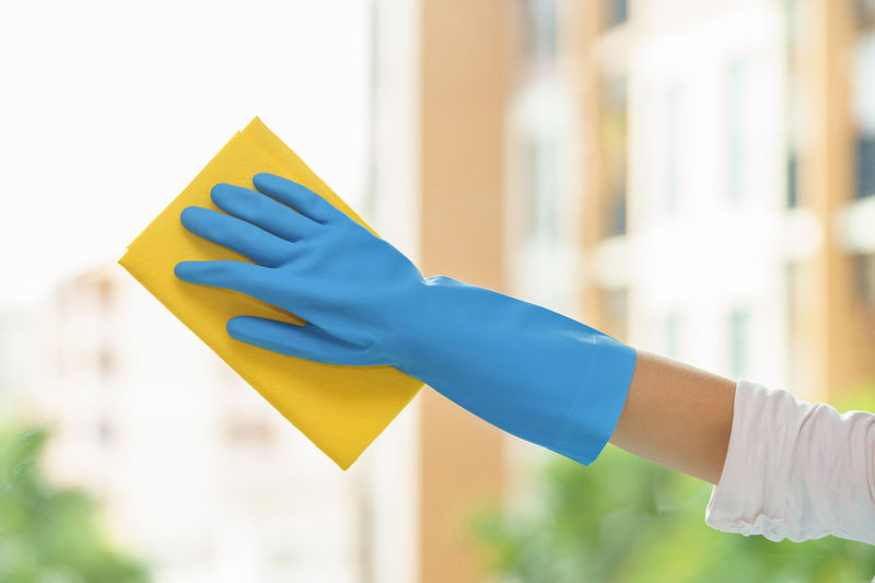 Cropped Hand Of Person Cleaning Glass Window At Home