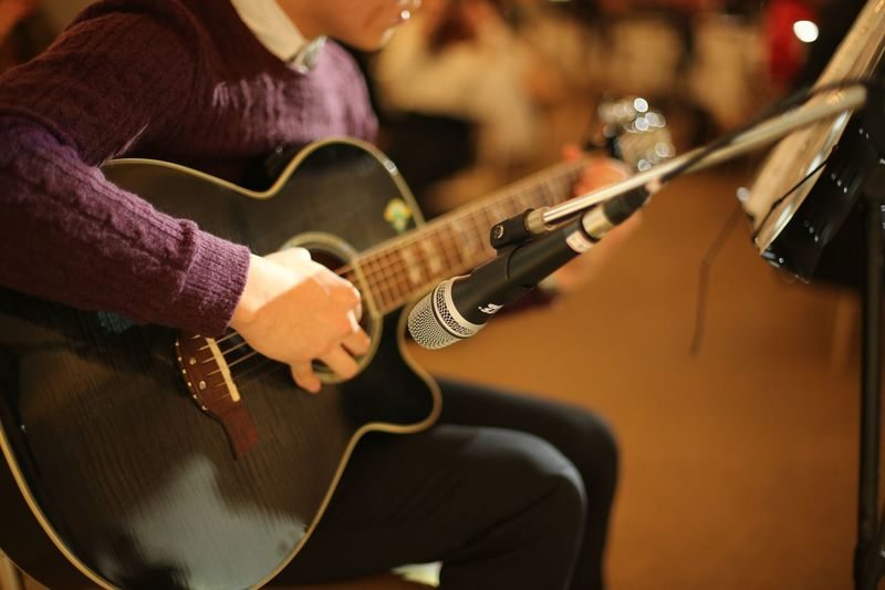 Musical performer tuning guitar on stage