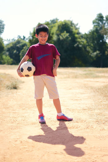 32f00b2a0d6 Smiling Boy Holding Soccer Ball While Standing On Field