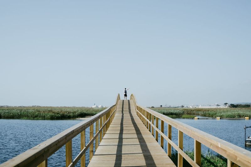 Rear view of young man with backpack standing on footbridge over river against clear sky