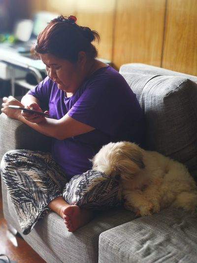 Woman Using Mobile Phone While Sitting On Sofa At Home