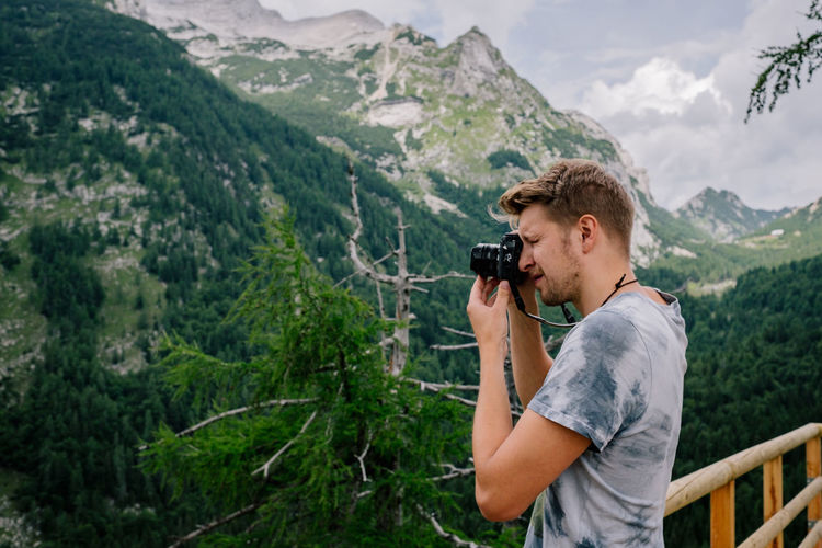 Side view of man photographing mountains