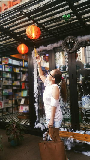 Side View Of Woman Touching Lantern Hanging In Store