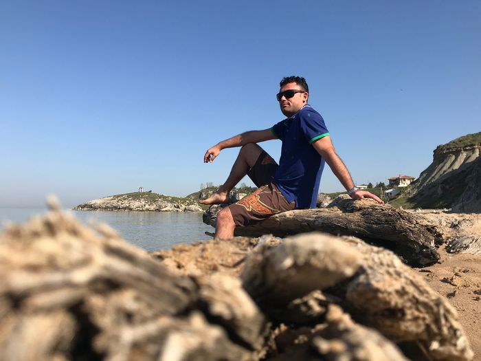 Full length of man sitting on rock at beach against clear blue sky