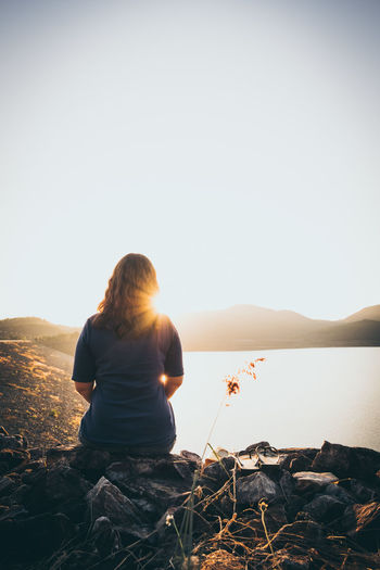 Rear View Of Woman Sitting On Shore Against Clear Sky
