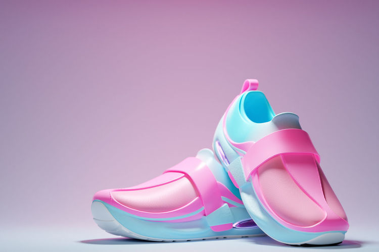 Close-up of pink shoes over white background