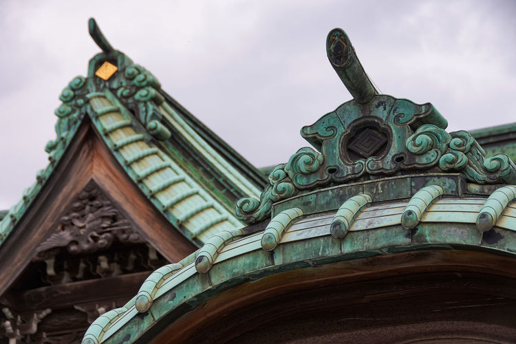 Low angle view of roof tiles and decoration on japanese temple against sky