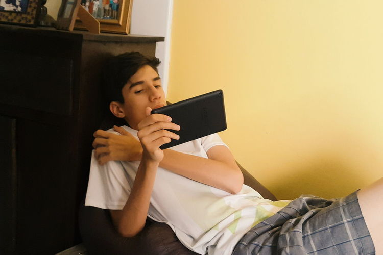 Teenager engaged with his tablet. One Person Wireless Technology Indoors  People Domestic Life Childhood Learning Technology Young Adult Tablet Teenager Life Teenager Wireless Device