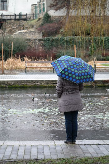 Rear view of woman with umbrella on wet footpath during rainy season