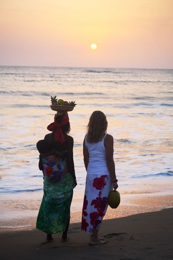 Rear View Of Woman With Friend And Daughter Standing At Beach