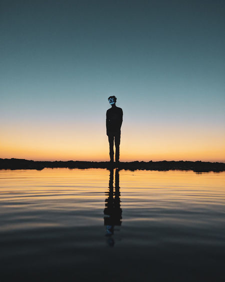 Silhouette man wearing mask standing by sea during sunset