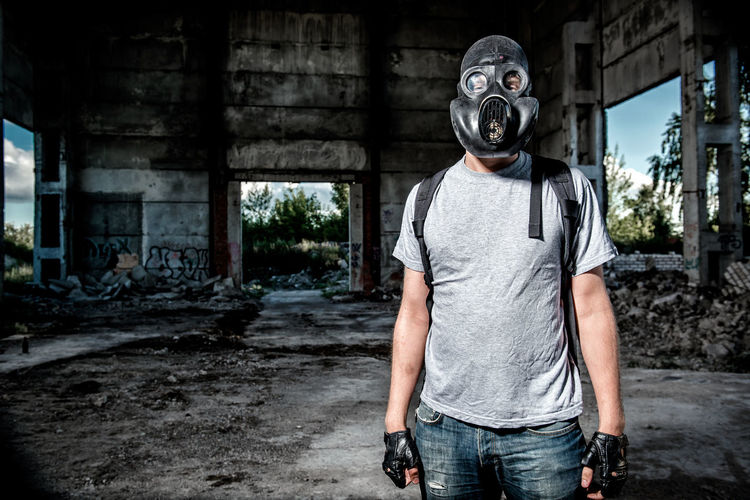 Man Wearing Gas Mask Standing Under Bridge