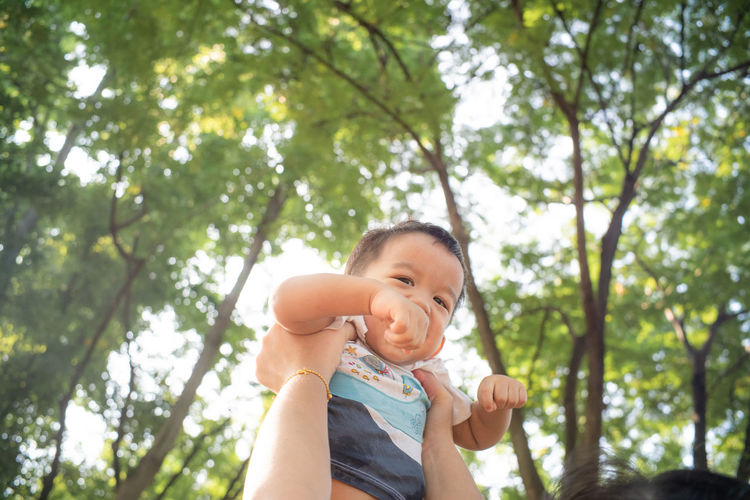 Low angle portrait of cute baby against trees