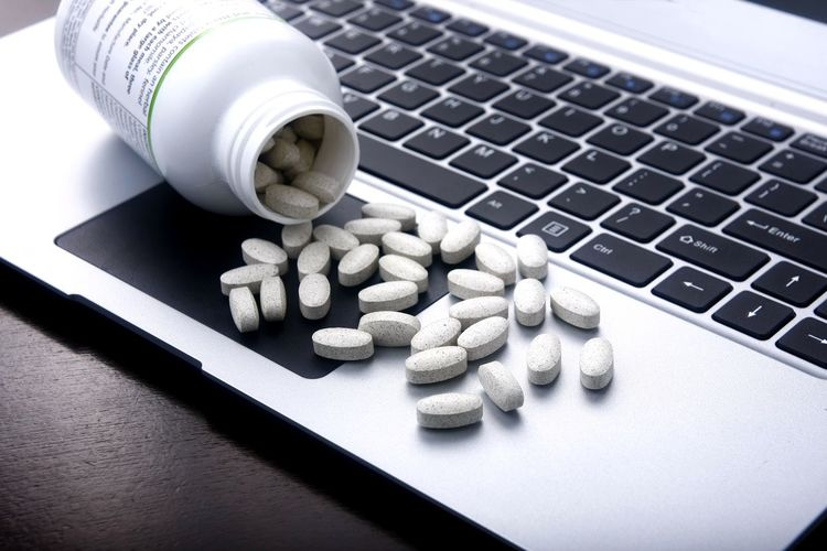 Medicine pills on a laptop computer keyboard. Laptop Keyboard Business Industry Ecommerce Online  Web Surf Internet Laptop Computer Computer Keyboard Technology Pharmacist Pharmaceutical Pharmacy Vitamins Cure Healthcare Healthcare And Medicine Health Capsule Tablets Pills Medical Medicine