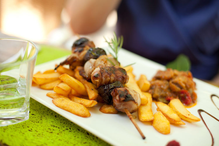 Close-Up Meat Skewer With French Fries And Ratatouille On Table