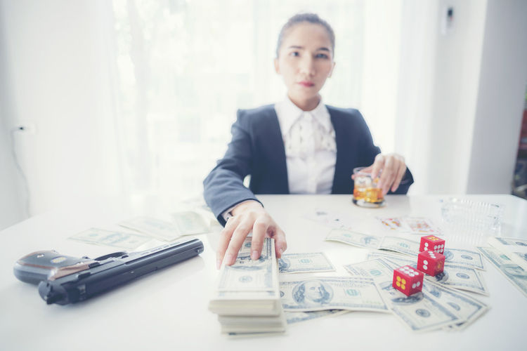 Businesswoman with paper currencies sitting at desk in office