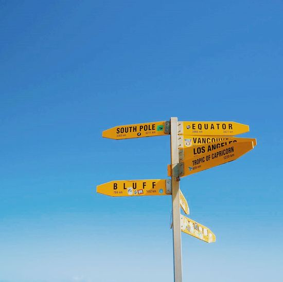 Guidance Sign Sign Board Journey Clear Sky Low Angle View No People Road Sign Information Sign Direction Blue Yellow Bright Courage Bold Lost Travel World Go Unsettled Planetary