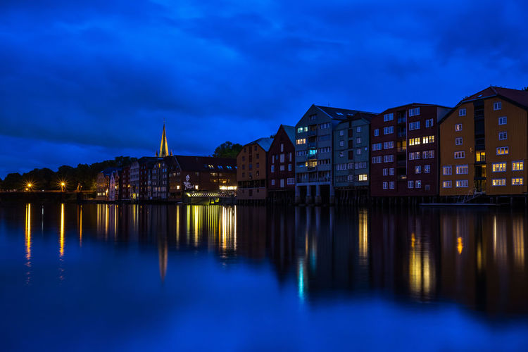 Trondheim cityscape at the blue hour with typical buildings along Nidelva River and the tower bell of Nidaros Cathedral in the background. Trondheim, Norway, Trondheim Norway Scandinavia Norwegian Northern Europe Building Exterior Architecture Built Structure Illuminated Reflection Building Sky City Water Dusk Night Waterfront Blue Nature No People River Cloud - Sky Residential District Outdoors