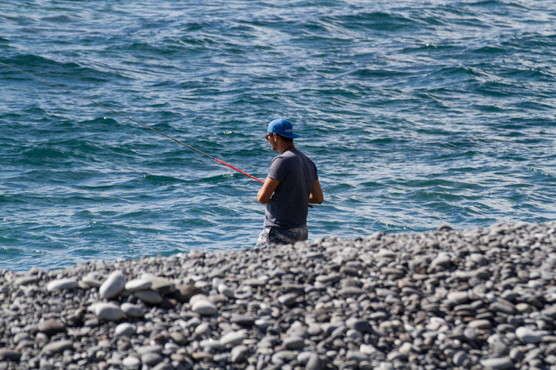 A guy with cap and sunglasses fishing Adult Beauty In Nature Cap Casual Clothing Day Fisherman Fishing Fishing Pole Fishing Tackle Full Length Horizon Over Water Leisure Activity Men Nature One Person Outdoors People Real People Rear View Rock - Object Sea Standing Summer Summertime Water