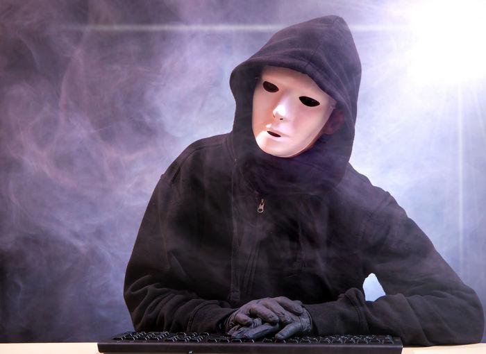 Computer hacker wearing mask and black hood