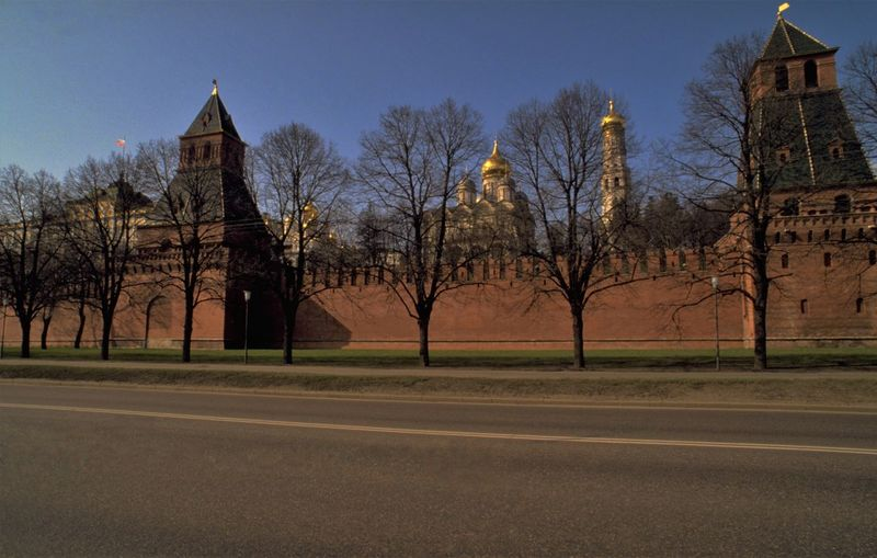 Outside the Russian Kremlin in Moscow. It is a sunny day in late winter. There is no longer snow on the ground but it is still very cold and spring feels a long way off. The lack of foliage on the trees allows us to see through to the golden onions of the Russian Kremlin Churches - the Assumption and Annunciation Cathedrals (left) and Archangel's Cathedral (centre). The Ivan the Great Bell Tower - said to mark the exact centre of Moscow - is the tall golden dome on the right. In Russia, the word Kremlin implies a medieval, inner-city fortress. In earlier times it would have probably meant a fortified town, or town surrounded by a wall. There are therefore a number of kremlins in Russia; although when we talk about The Kremlin, we usually mean where the workings of power take place in the Russian capital, Moscow. As well as being the official working residence of the Russian President, the Moscow Kremlin also houses Russia's main museum. The outer red brick wall of the Moscow Kremlin was built at the turn of the 15th and 16th centuries; replacing the earlier fire hazard, made of wood. The tower on the left is The Secret (Tainitskaya) Tower and to the left of that is The Grand Kremlin Palace. http://pics.travelnotes.org/ Architecture Blue Sky Cathedrals  Fortress Ivan The Great Bell Tower Kremlin Kremlin Palace Late Winter Michel Guntern Moscow No Leaves No People Palace Red Brick Wall Russia Russian Russian Kremlin Street Scene Neighborhood MapThe Kremlin Tourist Attraction  Travel Travel Photography Travel Photos Travel Pics