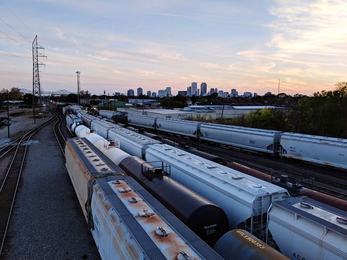 Trains on railroad tracks against sky during sunset