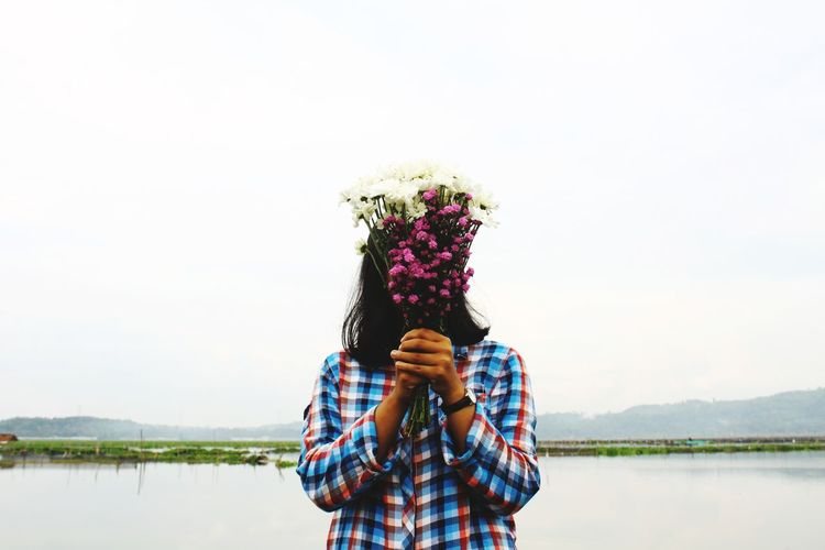 Woman Covering Face With Bouquet By Lake Against Clear Sky
