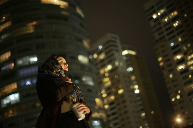 Low angle view of woman wearing hijab standing against illuminated buildings at night