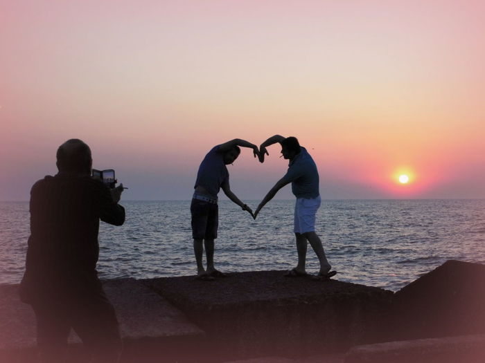 People forming heart of hand next to sunset against clear sky