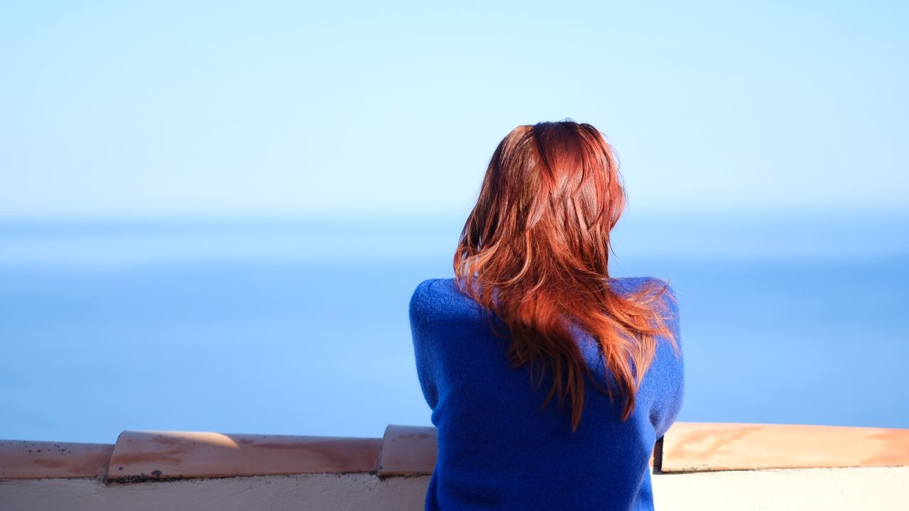 rear view, sea, blue, real people, horizon over water, water, one person, outdoors, day, nature, clear sky, standing, leisure activity, scenics, tranquility, women, sky, beauty in nature, young women, young adult