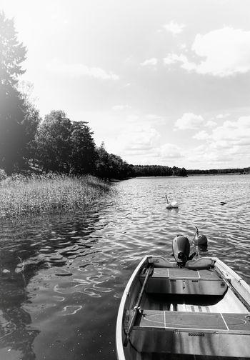 Boat floating on lake against sky