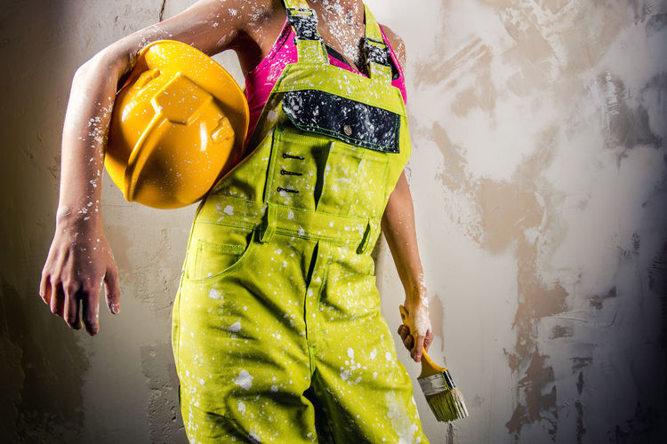 Midsection of woman coveralls holding paintbrush and hardhat against white wall