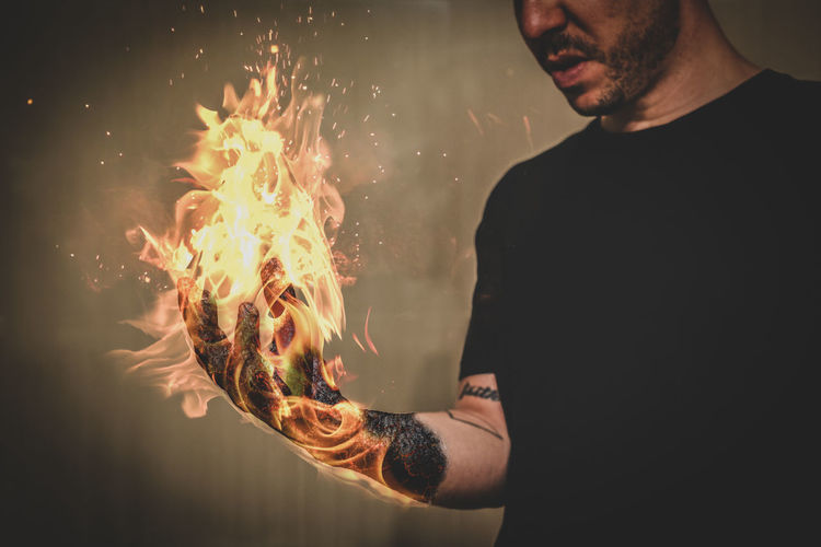 Digital composite image of person with burning hand while standing against wall